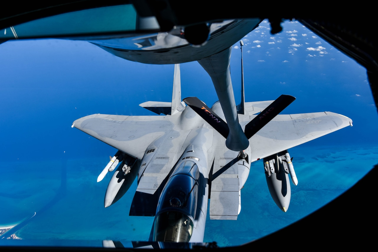 A plane et refuels a jet in midair.