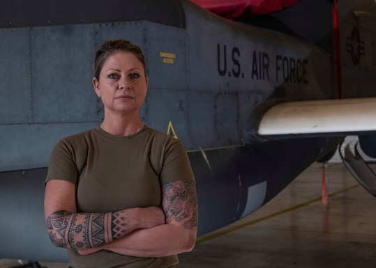 Senior Airman Jennifer Carrier stands in front of a Globalhawk