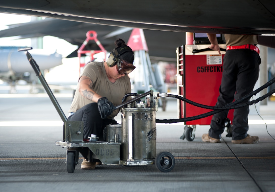 Senior Airman Reanna Holcomb, 154th Aircraft Maintenance Squadron assistant dedicated crew chief, services the oil of an F-22 Raptor