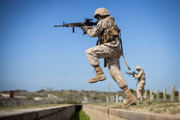 A Marine Corps recruit holds up a weapon while in midstep.
