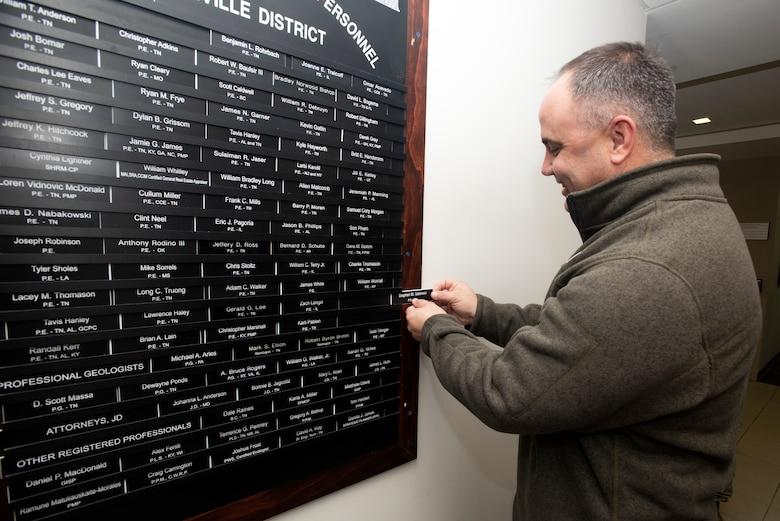 """Cory Morgan, U.S. Army Corps of Engineers Nashville District Structural Section chief, affixes a nameplate on behalf of Stephen M. Salaman, structural engineer, onto the """"Registered Professional Personnel"""" board as a record of his achievement during a ceremony Feb. 19, 2020 at the district headquarters in Nashville, Tennessee. Morgan supervises Salaman, who was unable to attend the ceremony, and who passed his exam in the state of Tennessee in October 2019. (USACE Photo by Lee Roberts)"""
