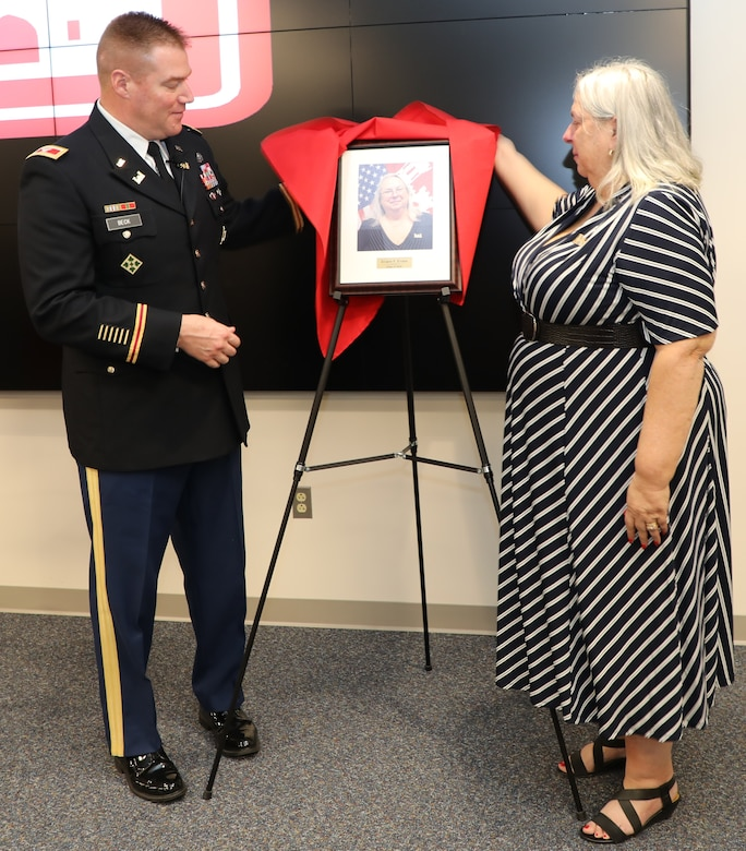 """Transatlantic Division Commander Col. Christopher Beck and Inductee Jo-Ann Evans unveil her portrait that will hang in TAD's """"Gallery of Distinguished Civilians."""" Evans and her former co-worker Donn Booker were inducted into the GoDC during a ceremony held Feb. 20, 2020 at TAD's Headquarters in Winchester, Va. The GoDC will be housed at TAD's headquarters, in the Executive Conference Room."""