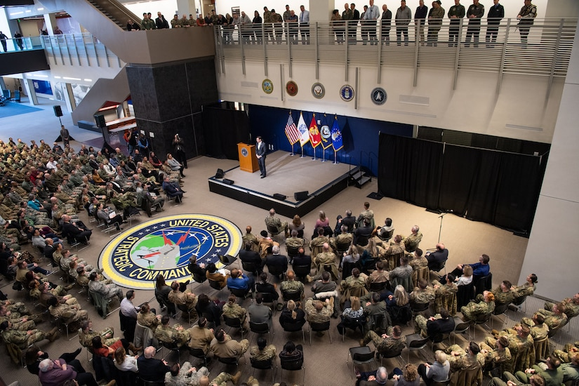 Defense Secretary Dr. Mark T. Esper stands on a stage speaking to an audience as seen from above.