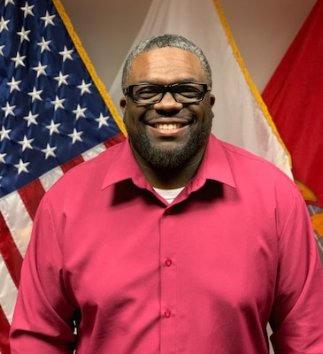 Photo depicts Bryant Daniels standing in front of a flag wearing a red shirt and glasses.