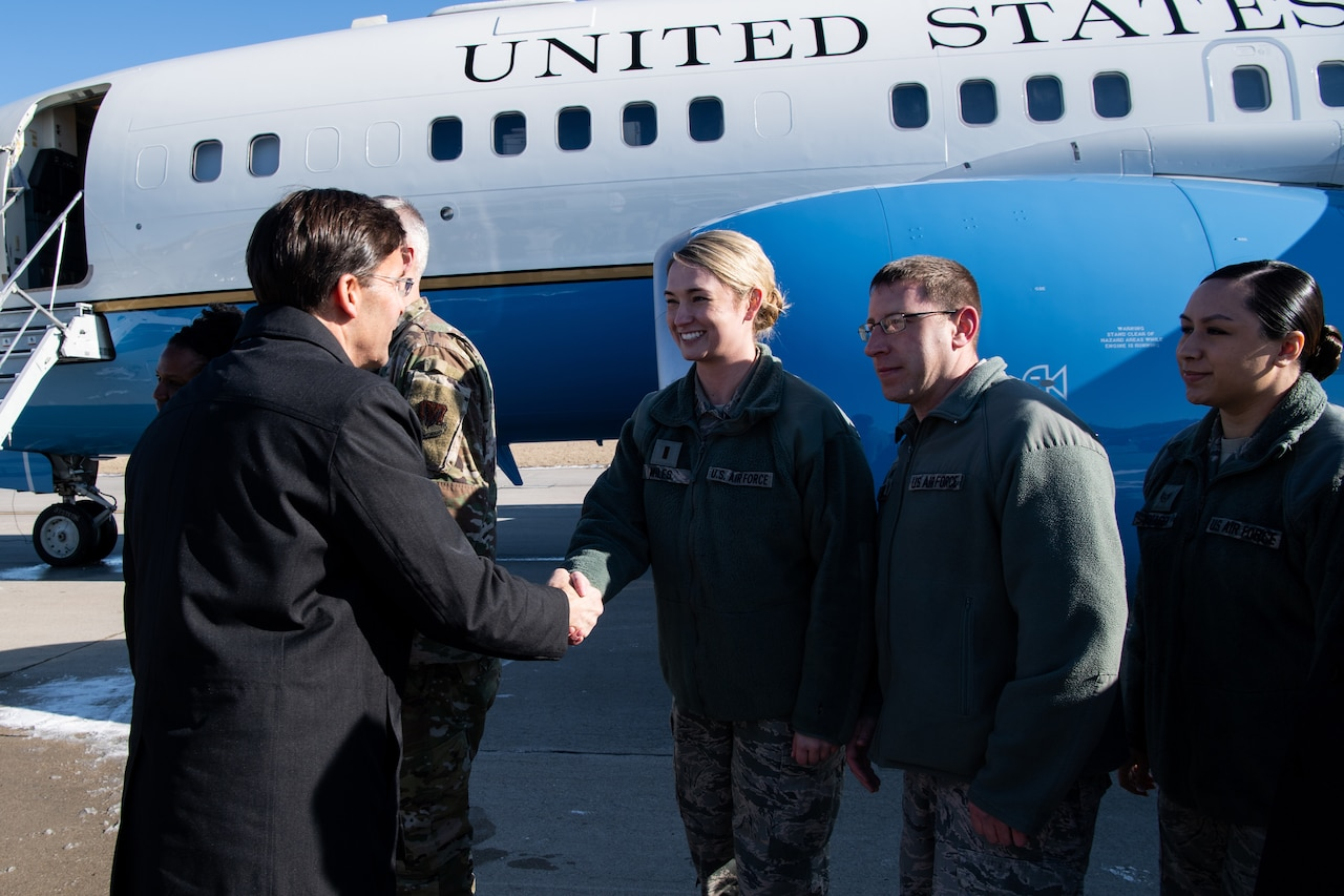 Defense Secretary Dr. Mark T. Esper shakes hands with airmen.