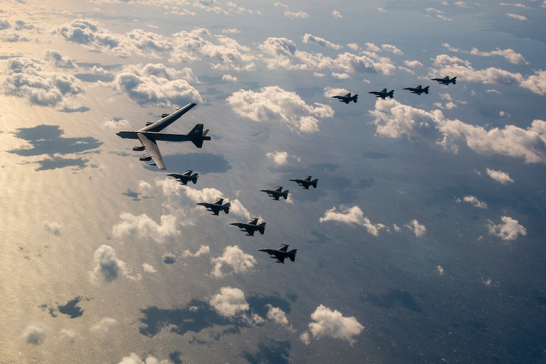 """Eleven aircraft fly in a """"V"""" formation over water in a cloud-studded sky."""