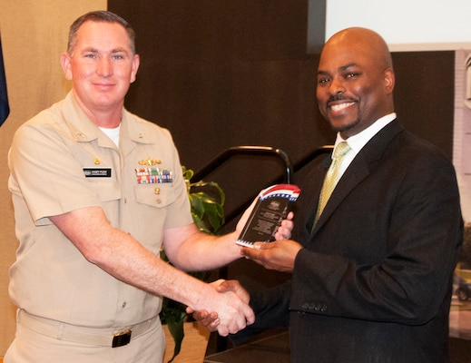 "KING GEORGE, Va. (Feb. 18, 2020) – Capt. Casey Plew, Naval Surface Warfare Center Dahlgren Division (NSWCDD) commanding officer, presents a plaque to Jimmy Smith – Department of the Navy Office of Small Business Programs director – in appreciation of Smith's keynote speech at the 2020 African American and Black History Month Observance. ""Lock in your morals,"" Smith advised the audience of military, government and contractors, attending the observance, while recounting his civilian career at the Naval Sea Systems Command. ""If you compromise yourself anywhere along the way, that means you will compromise yourself again later. Lock yourself into your morals.""  (Photo by U.S. Navy/Released)"