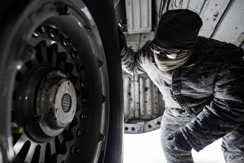 Crew chief inspects a wheel and tire assembly on a C-17 Globemaster III