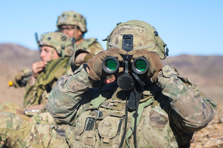 A soldier uses binoculars with others standing in the background.