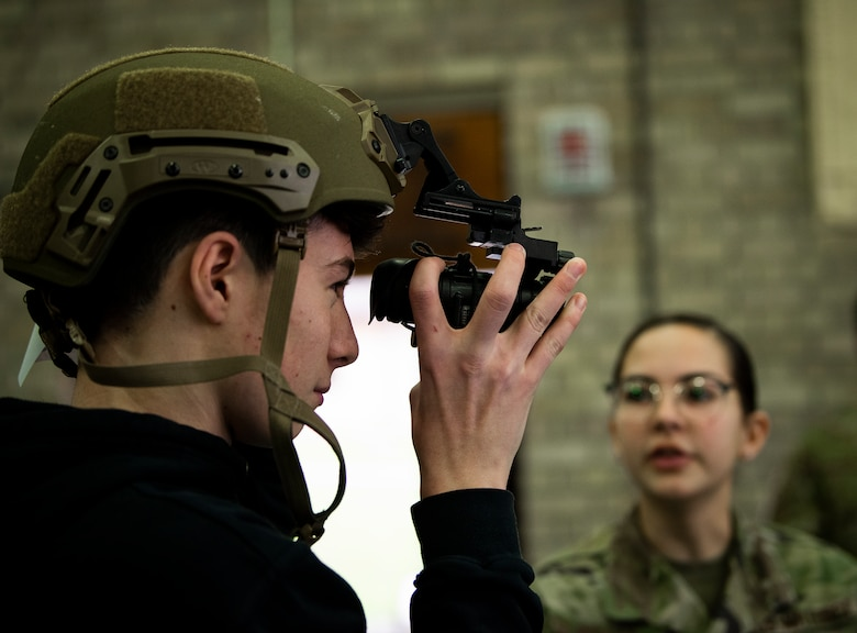 A student puts on security forces gear during a career fair