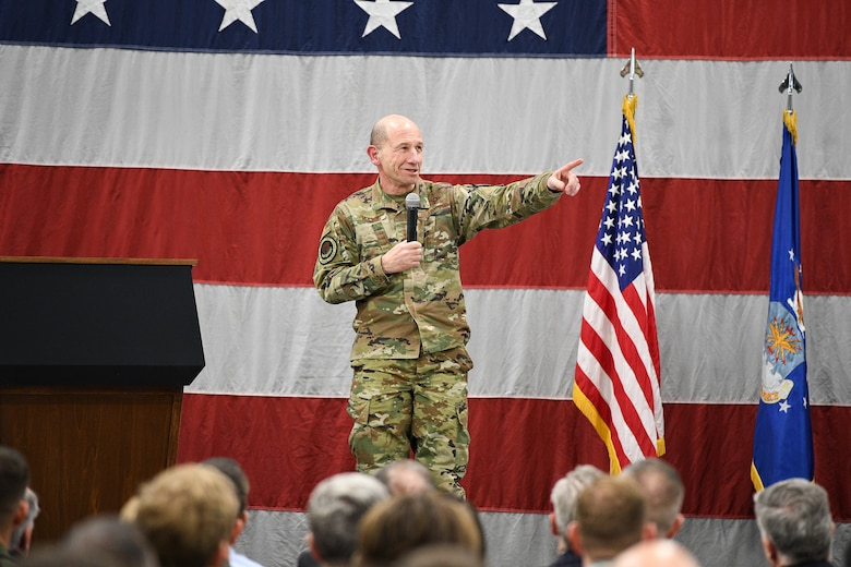 """Gen. Mike Holmes, commander of Air Combat Command, points during his F-35A """"full warfighting capability"""" ceremony presentation."""