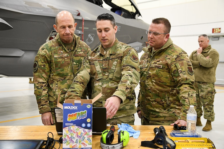 Tech. Sgt. Matthew Ruggiero (middle), 4th Aircraft Maintenance Unit, Gen. Mike Holmes, commander of Air Combat Command, left, and  Command Chief Master Sgt. David W. Wade, command chief of ACC, look over equipment on a table located in a hangar at Hill AFB. The nose of an F-35A Lightning II can be seen in the background.