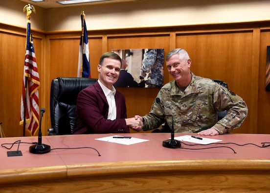 Superintendent of Schools Dr. Carl Dethloff and U.S. Air Force Col. Tony England, 17th Mission Support Group commander, shake hands after signing a memorandum of agreement, manifesting the 17th Training Wing to share vehicle mechanics and technicians with SAISD inside the San Angelo Independent School District Administration Building, in San Angelo, Texas, Feb. 21, 2020. Mission permitting and space available, 17 Logistics Readiness Squadron will provide the labor to perform maintenance and inspections on SAISD support vehicles. (U.S. Air Force photo by Airman 1st Class Abbey Rieves)