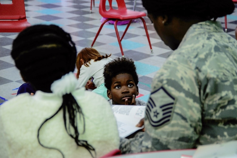 A Master Sgt. reads to a child at the Kirtland Youth Center.