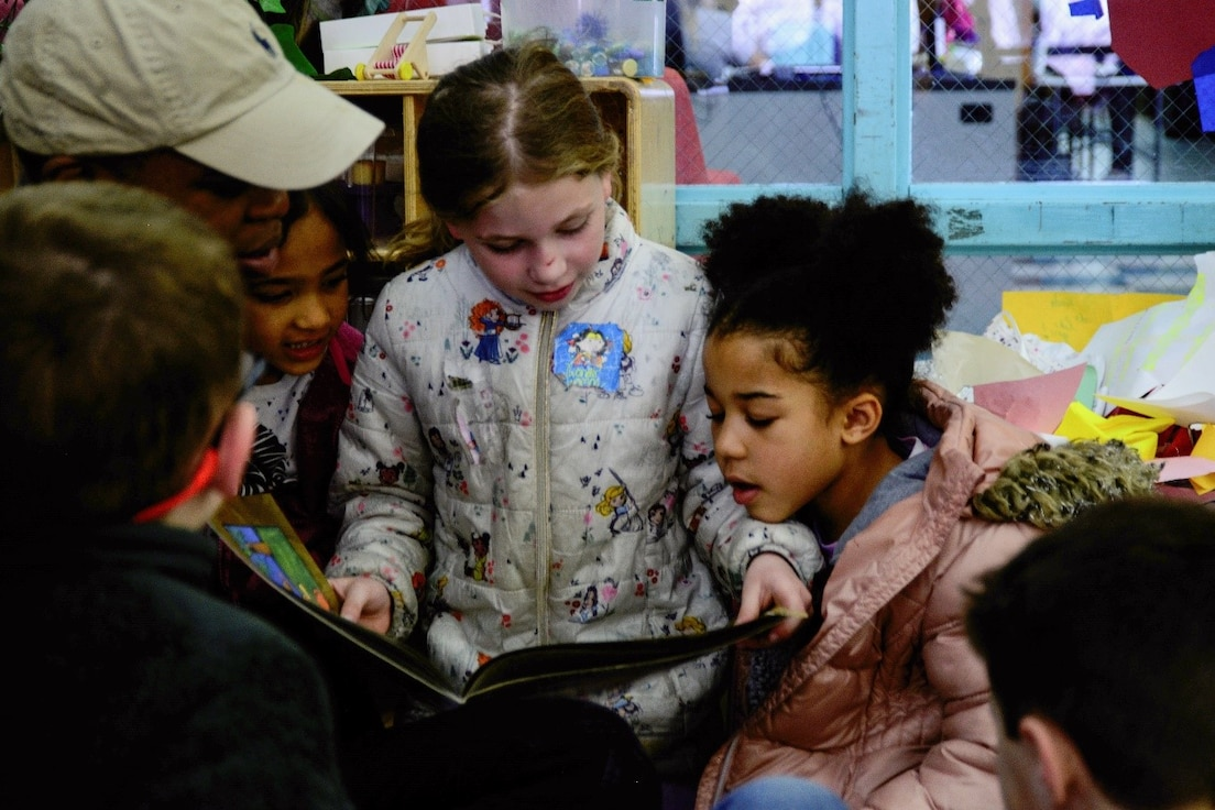 Children standing reading a book