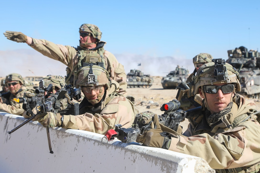 A soldier stands and gestures forward with one arm, while others hold up weapons from behind a barrier.