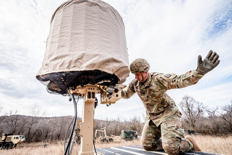 A soldier in uniform checks a radar while holding one hand up in the air.