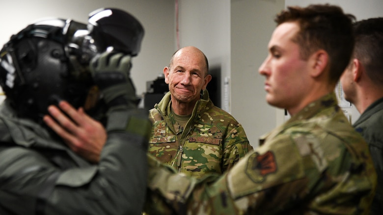Gen. Mike Holmes, commander of Air Combat Command, watches as an Airman puts on a helmet.