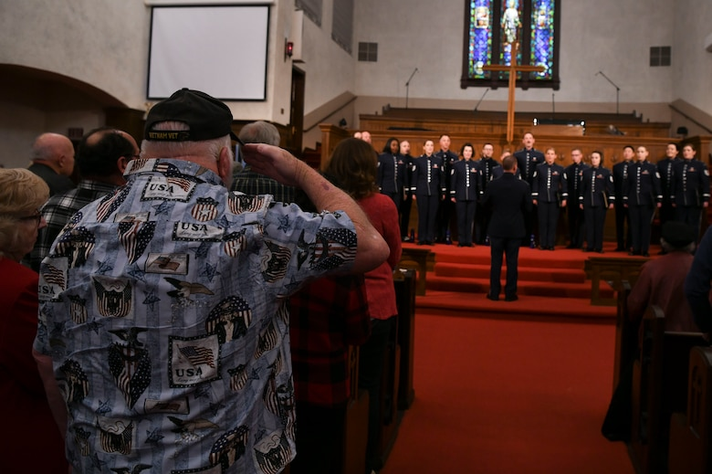 A U.S. Air Force veteran salutes during the signing of the national anthem at the beginning of a U.S. Air Force Band Singing Sergeants concert in Fullerton, Ca., Feb. 11, 2020. The singers perform the national anthem at the beginning of every concert. (U.S. Air Force photo by Airman 1st Class Spencer Slocum)