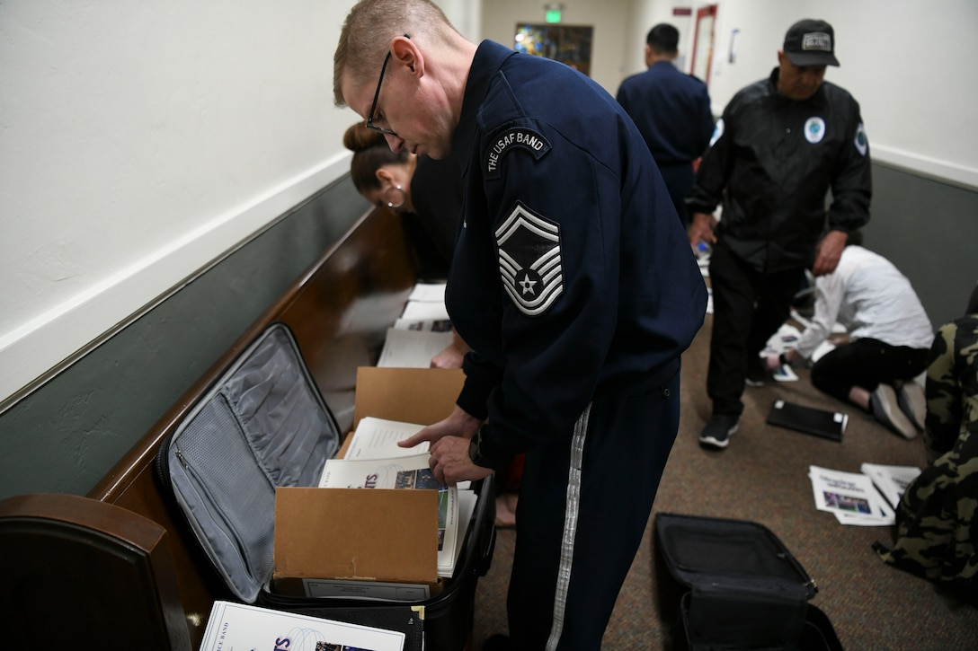 Senior Master Sgt. Ryan Dolan, U.S. Air Force Band Singing Sergeants bass vocalist, prepares programs to be distributed before a show in Fullerton, Ca., Feb. 11, 2020. The singers have a lot of preparation for shows outside of just rehearsing including preparing programs, selecting venues, managing travel plans and social media. (U.S. Air Force photo by Airman 1st Class Spencer Slocum)