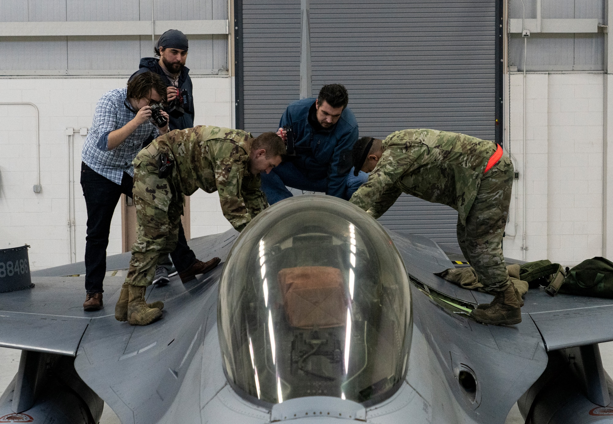 people standing by an F-16 airplance