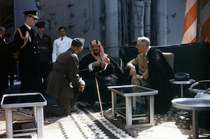 200221-N-NO101-155 WASHINGTON (Feb. 21, 2020) In this file photo taken Feb. 14, 1945, President Franklin Delano Roosevelt, right, and King Abdul Aziz Ibn Saud of Saudi Arabia confer aboard USS Quincy (CA 71). The monarch speaks to Col. Willaim A. Eddy, who interprets the conversation, and Fleet Adm. William D. Leahy is at left. (U.S. Army Signal Corps photo/Released)