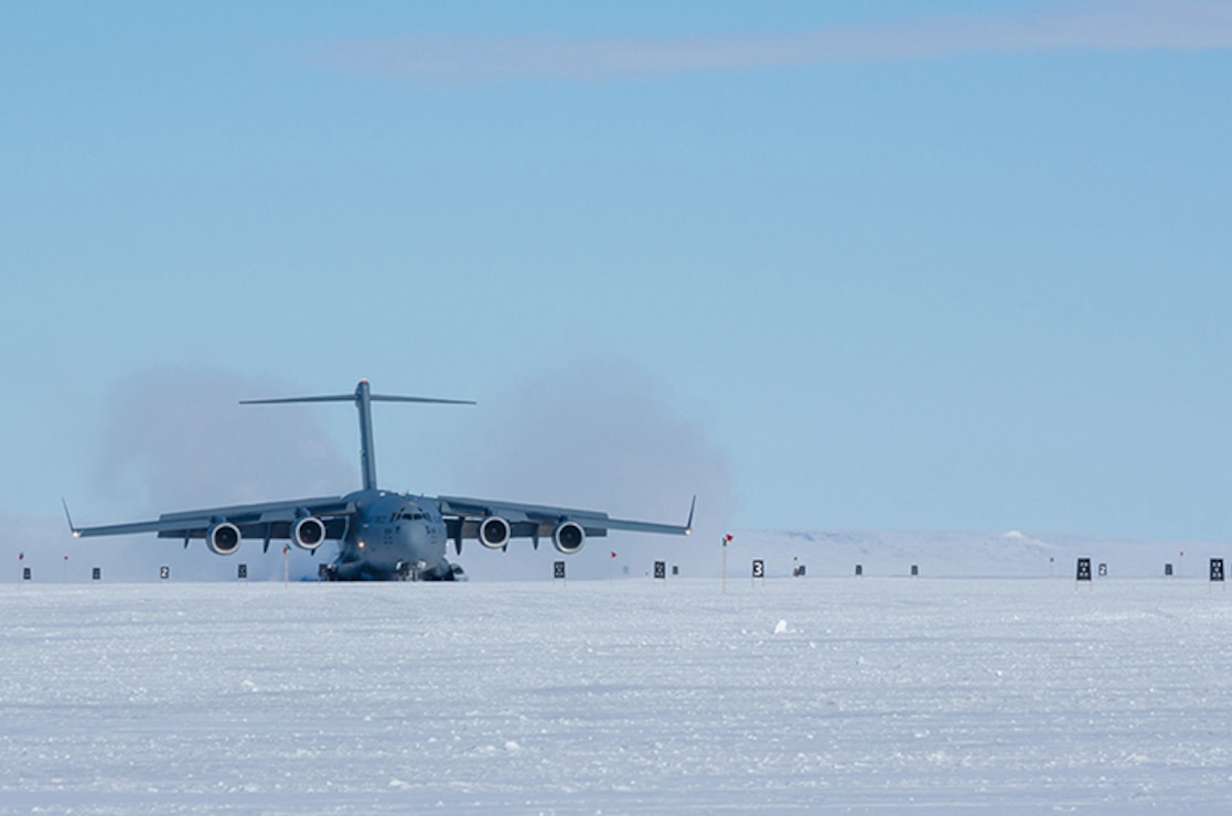 A plane lands on an icy runway.