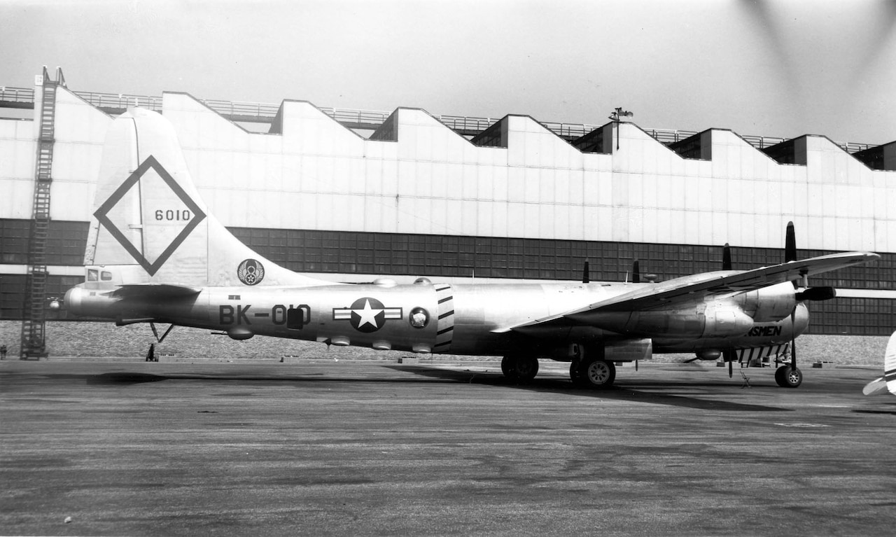A 1940s-era bomber aircraft with the number 6010 on its tail sits on the tarmac.
