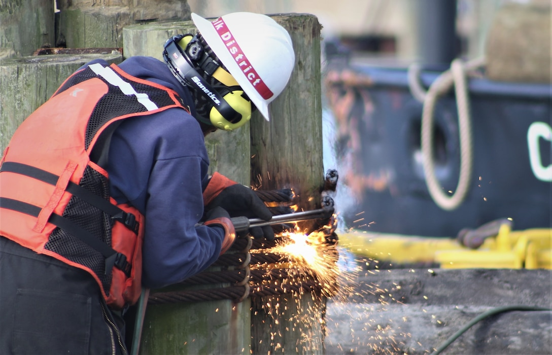 A man in a hardhat uses a torch to deconstruct wooden pilings in Rudee Inlet