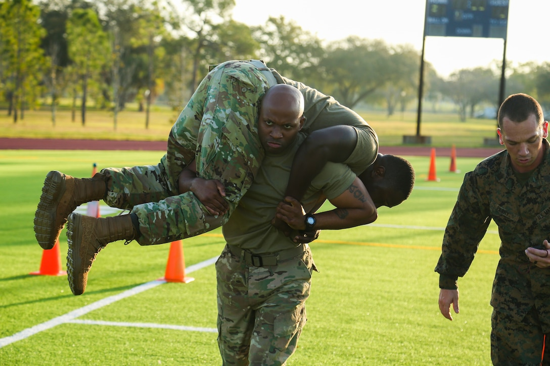 U.S. Army Staff Sgt. Charles Brice transports U.S. Air Force Master Sgt. Houston Pettway using a fireman's carry during the fitness portion of U.S. Central Command's annual Service Member of the Year (SMOY) competition, February, 18, 2020. The event tests physical fitness, service knowledge, professional knowledge, military bearing, and character of competing service members. (U.S. Central Command Public Affairs photo by Tom Gagnier)