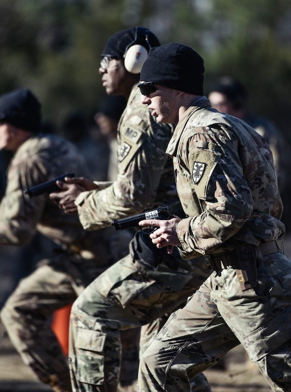 U.S. Army Sgt. Jacob Beardmore and Sgt. 1st Class Tyrone Smith, 7th Transportation Brigade (Expeditionary), draw their weapons during a Dynamic Shooting Drill at Joint Base Langley-Eustis, Virginia, Jan. 27, 2020.