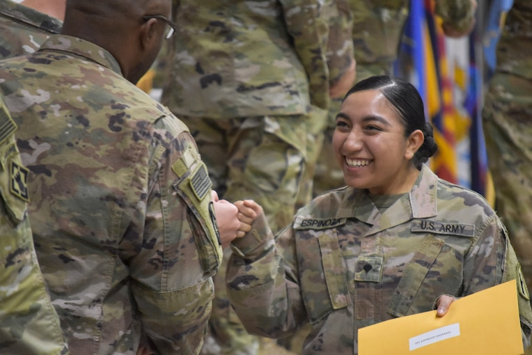 A smiling soldier fist-bumps another.