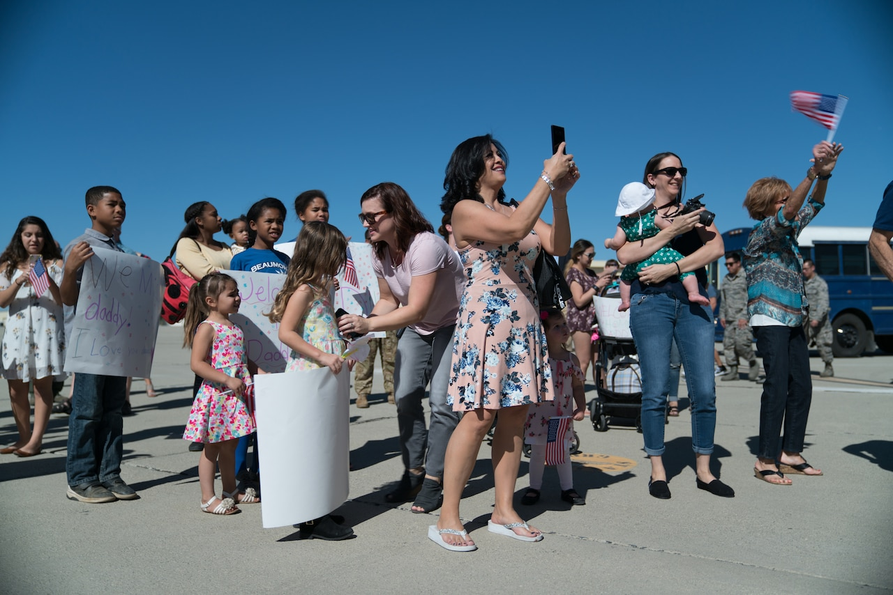 "Children and women stand in a group. Many are holding cameras and carrying ""Welcome Home"" signs."