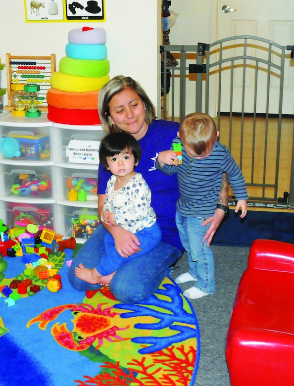 A woman provides child care to two children.