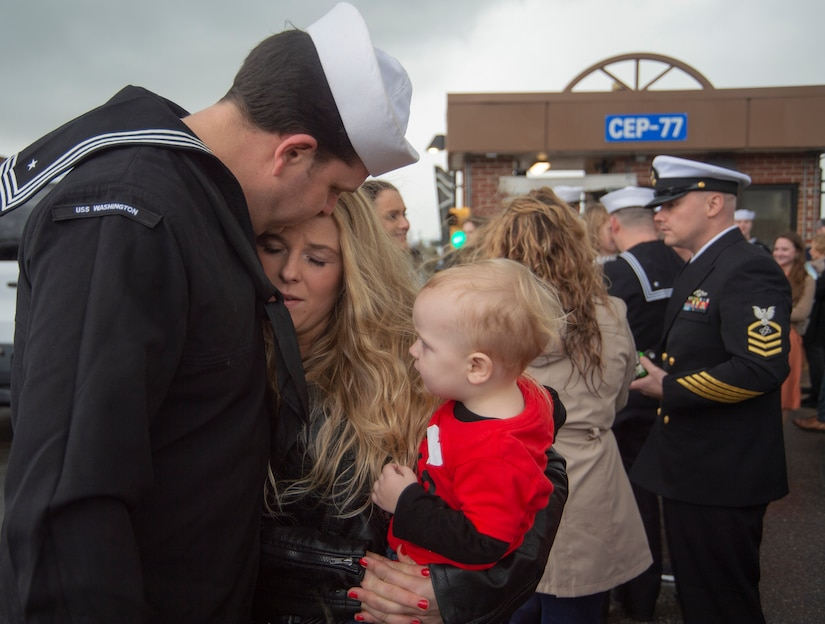 A service member hugs a woman and child.