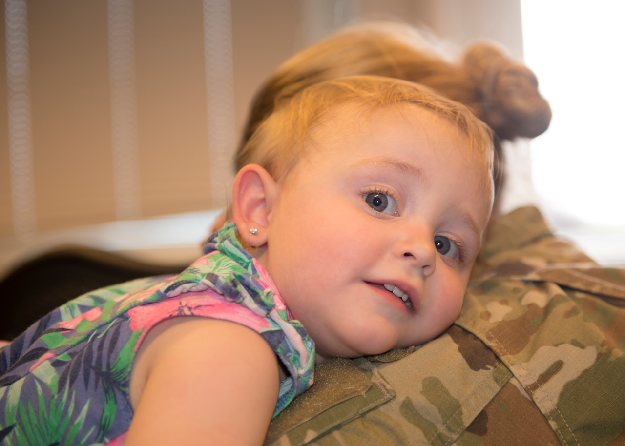 A small child rests her head on a service member's shoulder.