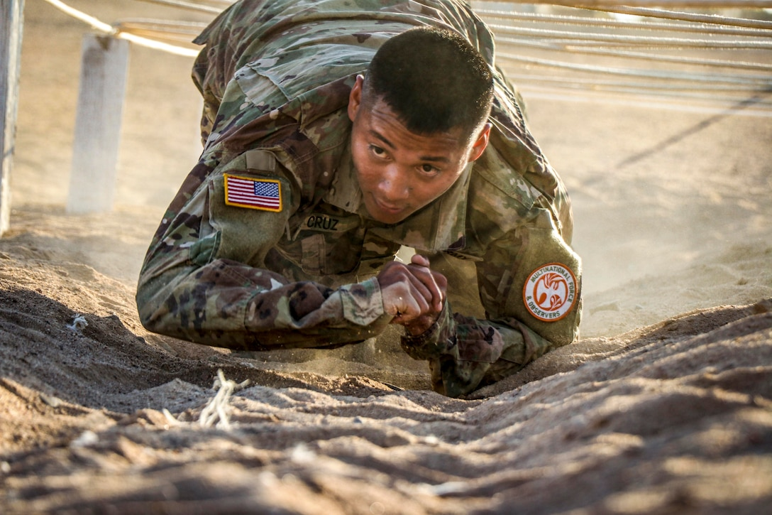 A soldier is crawling under ropes.