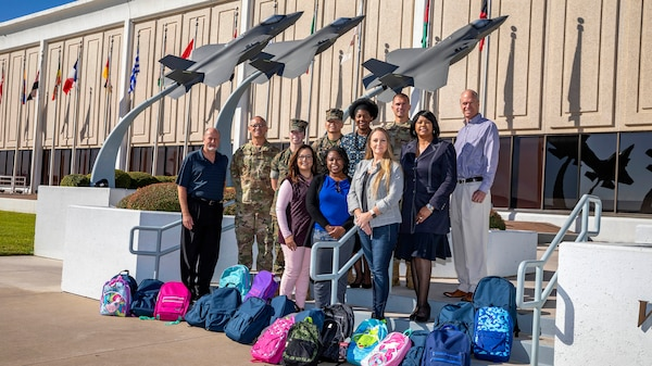 DCMA team stands on stairs in front of donated supplies.