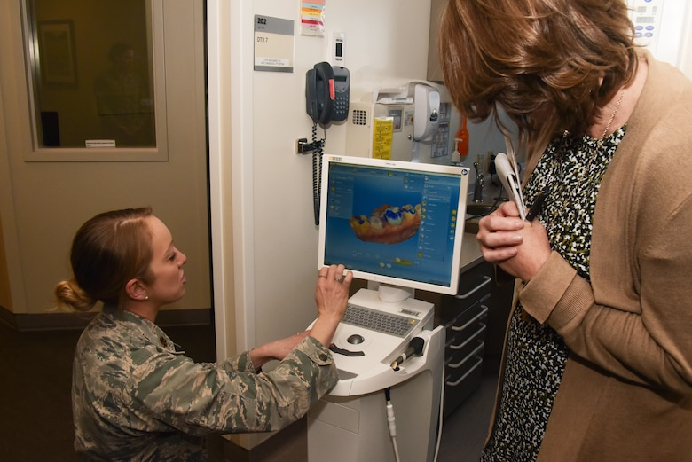 Maj. Cassidy A. Mennen, 460th Medical Group Dental flight commander, shows Mrs. Tonia Shaw, the Combined Force Space Component commander, U.S. Space Command spouse, a computer that helps model dental services for clients at Buckley Air Force Base, Colo. Feb. 21, 2020.