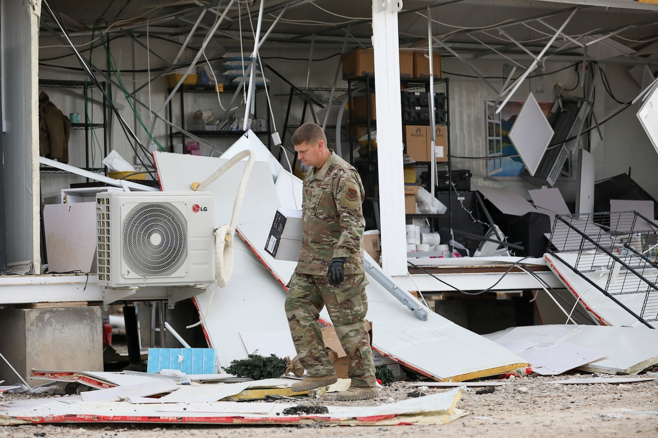Airman walks through debris.