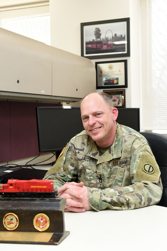 Army Reserve Sgt. 1st Class James Jacobs, Training NCO, Headquarters & Headquarters Company, 85th U.S. Army Reserve Support Command, pauses for a photo at his desk. Jacobs is an 88 Uniform (Railway Specialist) with more than 20 years of experience in Army rail operations.