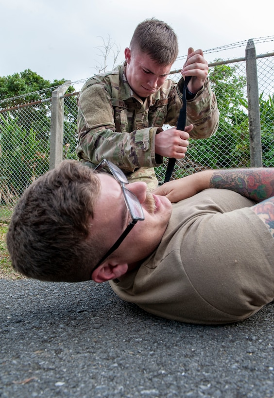 U.S. Air Force Airman 1st Class Kevin Kovach, 18th Security Forces Squadron response force leader, places a tourniquet on the simulated patient's arm during the Defenders Challenge Feb. 13, 2020, at Kadena Air Base, Japan. This was one of several events participants had to overcome during the Defenders Challenge varying from physical exercise, a three-mile run, to weapon assembly. (U.S. Air Force photo by Naoto Anazawa)