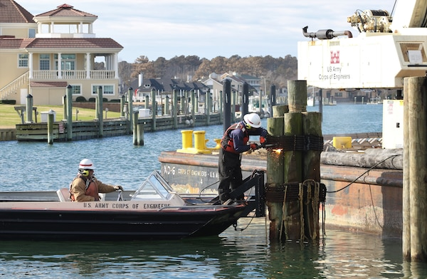 One man steers a boat while the other uses a torch to deconstruct wooden pilings in Rudee Inlet