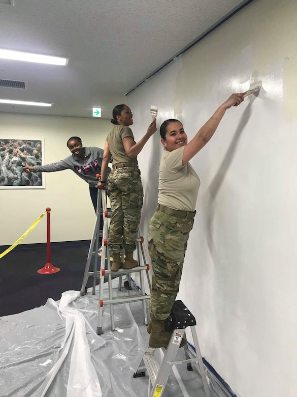 (From right) Senior Airman Karen Villalobos, 374th Security Forces Squadron pass and registration clerk, Tech. Sgt. Latisha Langley, 374 SFS NCO in charge of pass and registration office, and Airman 1st Class Te'Anne Dailey, 374 SFS patrolman, apply primer to a wall before painting a mural at Yokota Air Base, Japan, Jan. 31, 2020.