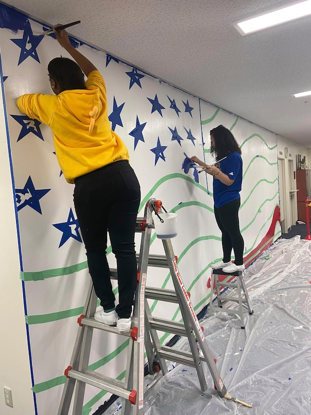 (Left to right) Airman 1st Class Te'Anne Dailey, and Airman 1st Class Deborah Kang, both 374th Security Forces Squadron patrolman, paint a mural at a main lobby of SFS's building at Yokota Air Base, Japan, Feb. 2, 2020.