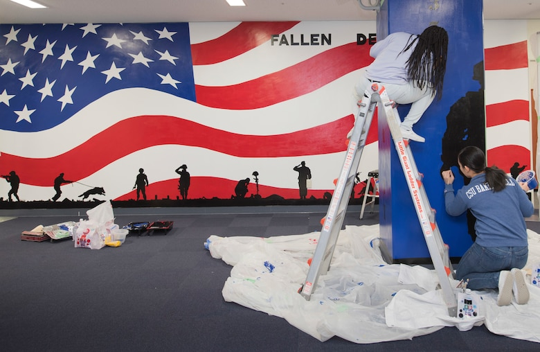 (Left to right) Airman 1st Class Te'Anne Dailey, and Airman 1st Class Deborah Kang, both 374th Security Forces Squadron patrolman, paint a mural at a main lobby of SFS's building at Yokota Air Base, Japan, Feb. 7, 2020.
