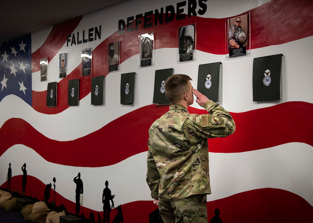 Airman 1st Class Jake Barnett, 374th Security Forces Squadron patrolman, salutes a photo of security forces airmen who fell in the line of duty, during a mural unveiling ceremony at Yokota Air Base, Japan, Feb. 21, 2020.
