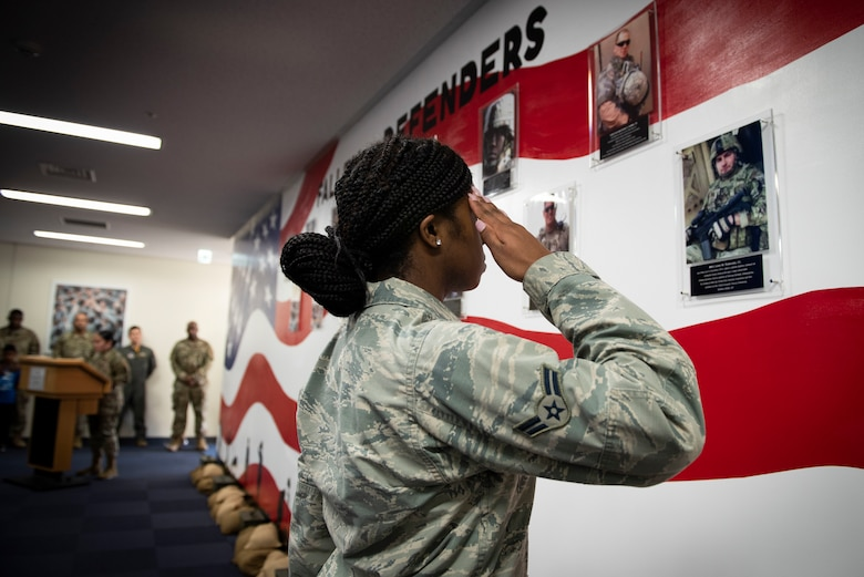 Airman 1st Class Wanisha Spence, 374th Security Forces Squadron patrolman, salutes a photo of security forces airmen who fell in the line of duty, during a mural unveiling ceremony at Yokota Air Base, Japan, Feb. 21, 2020.