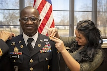 """Maj. Tatchie Manso, 1st Theater Sustainment Command, smiles as Elena, Manso's wife, pins on his new rank during a ceremony at Fort Knox, Ky., Dec. 11, 2019. The Army recently initiated changes to its promotion process, allowing qualified officers a chance to """"opt-in"""" for early promotion consideration. Qualified captains can also opt out of promotion to pursue career-broadening assignments, or other advanced educational or key developmental opportunities -- in the best interest of the Army. (Photo Credit: Spc. Zoran Raduka)"""