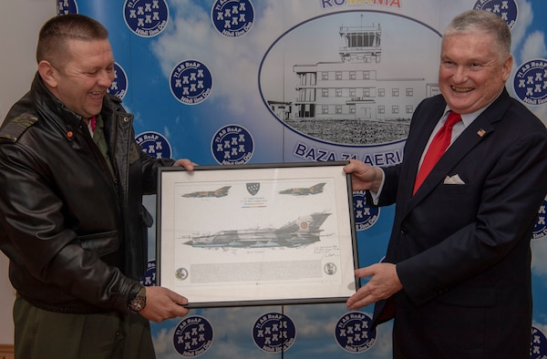 Romanian Air Force Col. Marius Oatu, 71st Air Base commander, left, presents a MiG-21 Lancer lithograph to Adrian Zuckerman, U.S. Ambassador to Romania, right, at the 71st Air Base, Romania, February 18, 2020. The 71st AB is home to a squadron of MiG-21 Lancers. (U.S. Air Force photo by Senior Airman Kyle Cope)